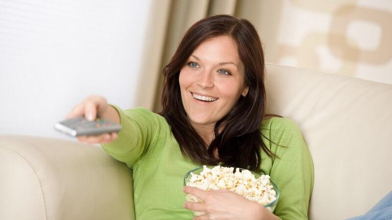 Junge Frau mit Popcorn auf Couch, schaut Fernsehen