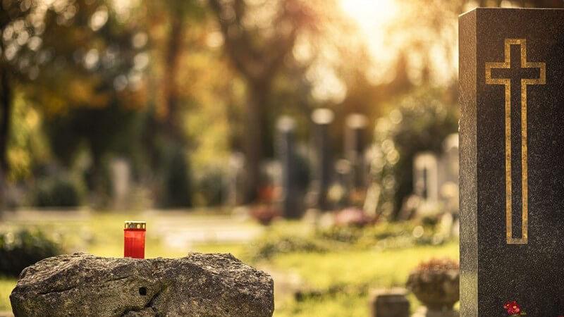 Friedhof bei Sonnenuntergang, Grablicht auf einem Stein neben einem Grabstein mit Kreuz drauf