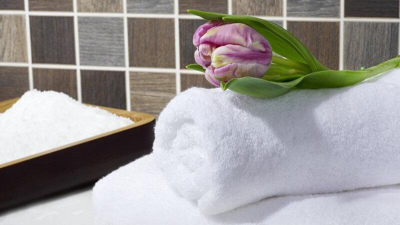 Badesalz, weiße Handtücher und Tulpe