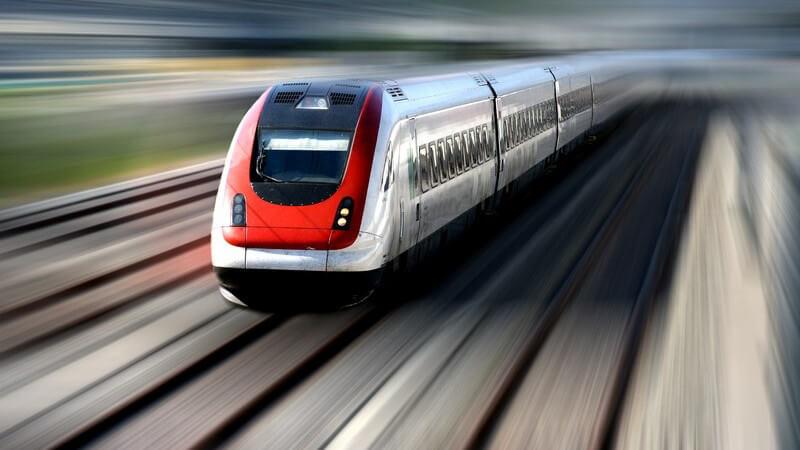 Zug ICE, der mit hoher Geschwindigkeit auf Gleisen fährt, Umgebung unscharf
