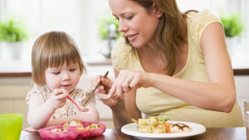 Schwangere Frau mit kleiner Tochter beim Essen