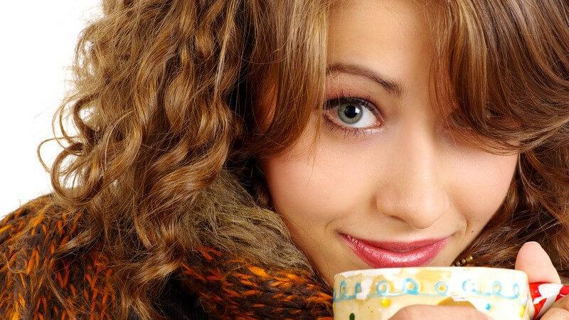 Junge Frau mit Schal schaut hinter ihrem Kaffeebecher vor und lächelt in Kamera