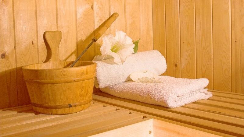 Saunaeimer mit Löffel, weißen Handtüchern und weißer Lilie auf einer Saunabank