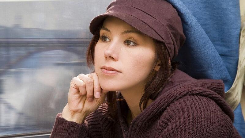 Brünette Frau mit brauner Mütze sitzt Verträumt am Zugfenster, im Hintergrund eine Brücke