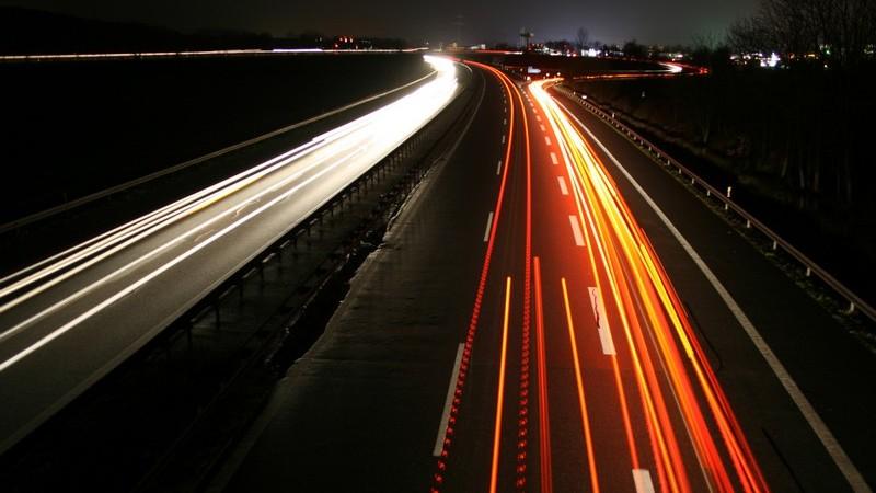 Autobahn bei Nacht von oben: fahrende Autos hinterlassen leuchtende Lichtstreifen