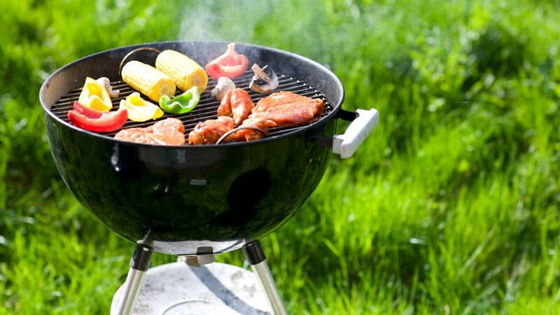 Grill auf Wiese mit Fleisch, Maiskolben, Gemüse