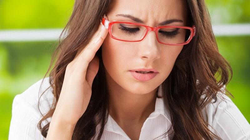 Müde, gestresste Geschäftsfrau mit Kopfschmerzen fasst sich an die Schläfe