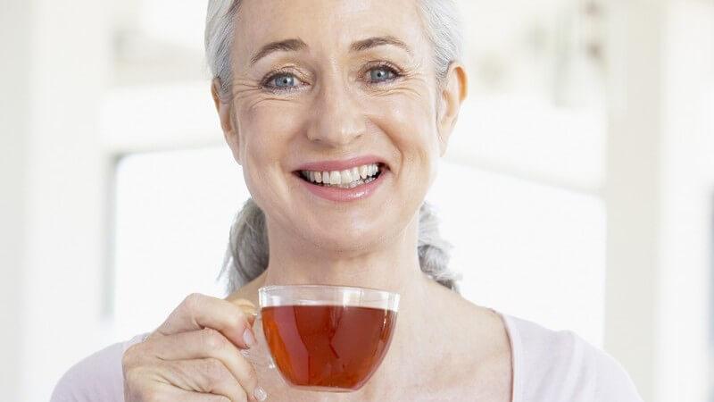 Ältere Frau hält Glas mit Tee in Hand und lacht in Kamera
