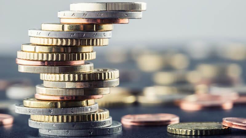 Aufeinander gestapelte Euro-Geldstücke neben weiteren Münzen