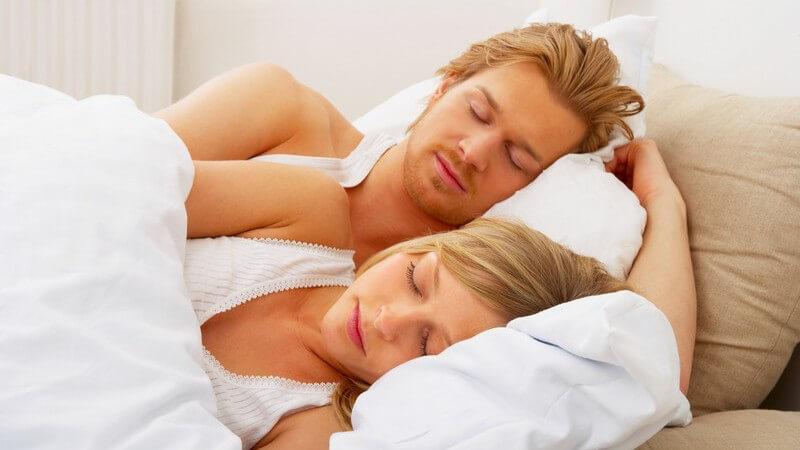 Blondes Paar liegt schlafend in weißem Bett