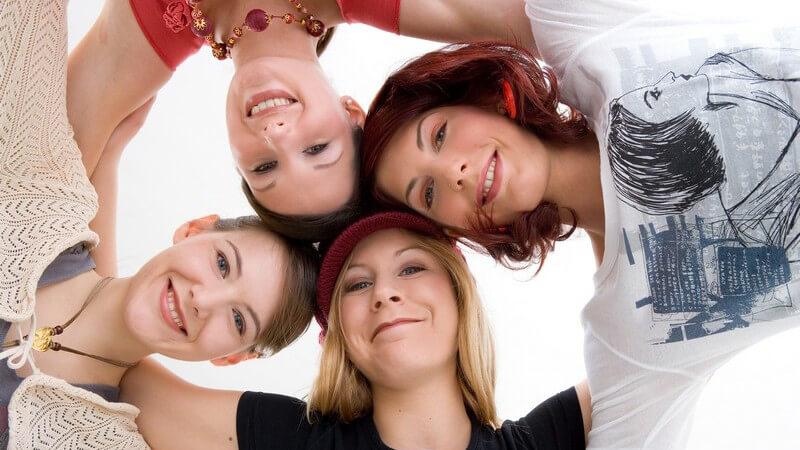 4 Frauen mit unterschiedlichen Haarfarben stecken ihre Köpfe zusammen, von unten fotografiert