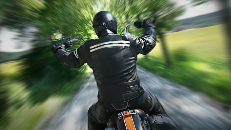 Rückenansicht Motorradfahrer fährt durch Allee
