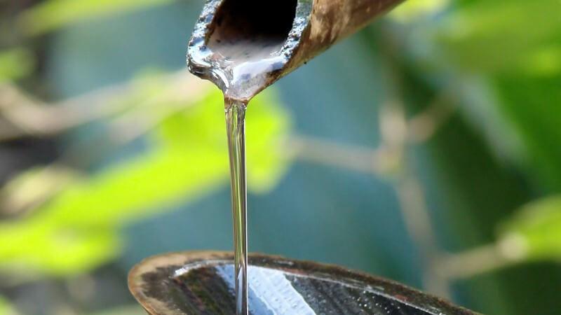 Wasser fließt aus einem Holzrohr einer natürlichen Quelle