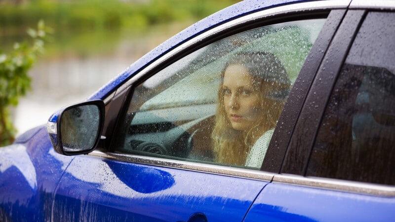 Junge Frau sitzt im blauen Auto und schaut aus Fenster, draußen regnet es