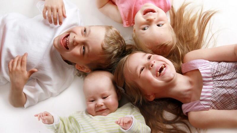 Ein Baby und drei kleine Kinder Kopf an Kopf auf dem Rücken liegend