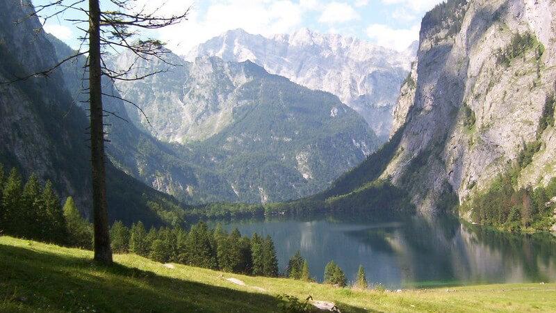 Naturaufnahme Gebirgsee umgeben von Bergen und Wiese