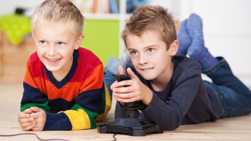 Zwei Jungen liegen auf dem Boden und spielen Videospiel mit Konsole