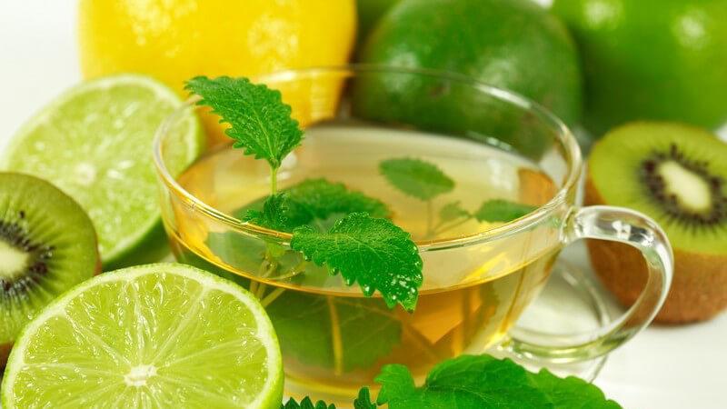 Grüner Tee im Glas, daneben aufgeschnittene Limetten und Kiwis