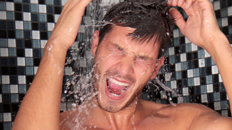 Mann mit offenem Mund und hochgehobenen Armen unter der Dusche