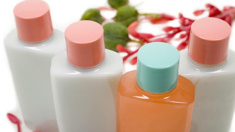 Vier Kosmetikflaschen mit Shampoo, Lotions oder Duschgel auf weißem Hintergrund