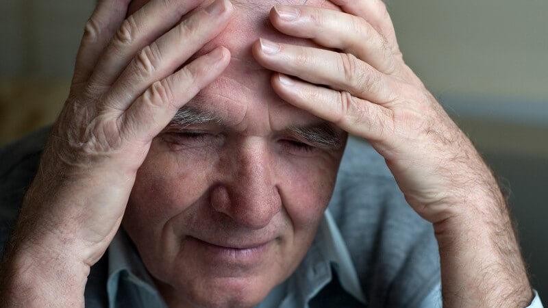 Alter Mann mit Kopfschmerzen fasst sich mit beiden Händen an die Stirn