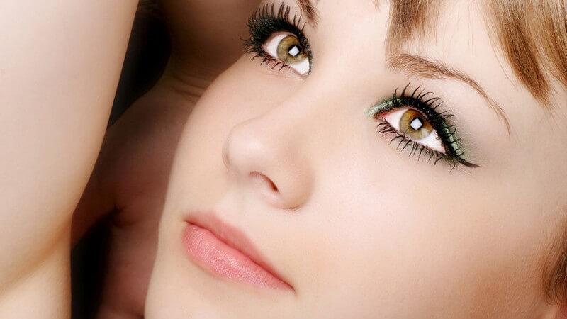Gesicht einer jungen Frau mit betonten, geschminkten, braunen Augen