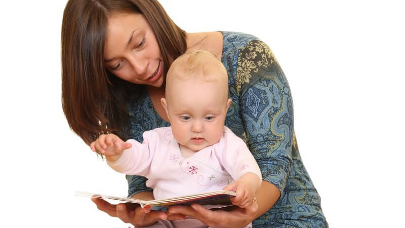 Junge Mutter hat Baby auf Schoß, schauen gemeinsam Bilderbuch an