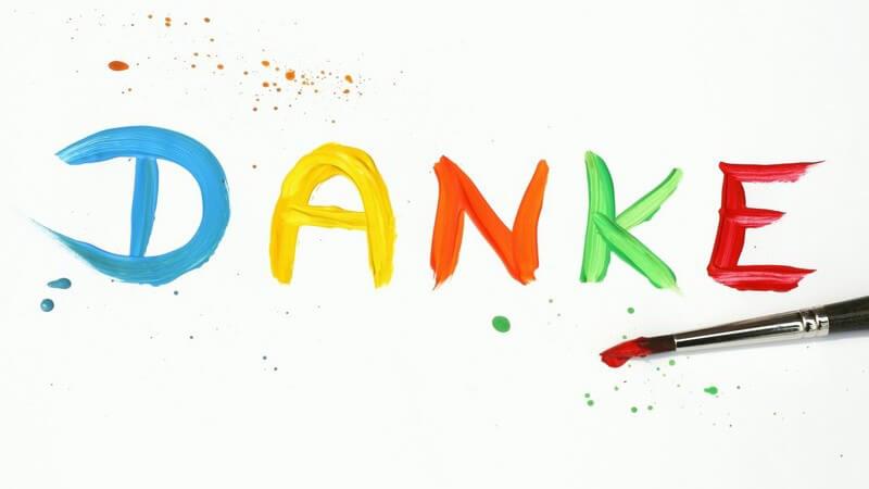 Das Wort Danke mit bunten Wasserfarben auf weißen Hintergrund gepinselt, darunter Pinsel