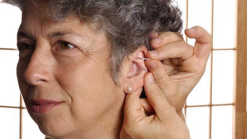 Ältere Frau mit kurzen, grauen Haaren und Perlenohrring erhält eine Akupunktur in die Ohrmuschel
