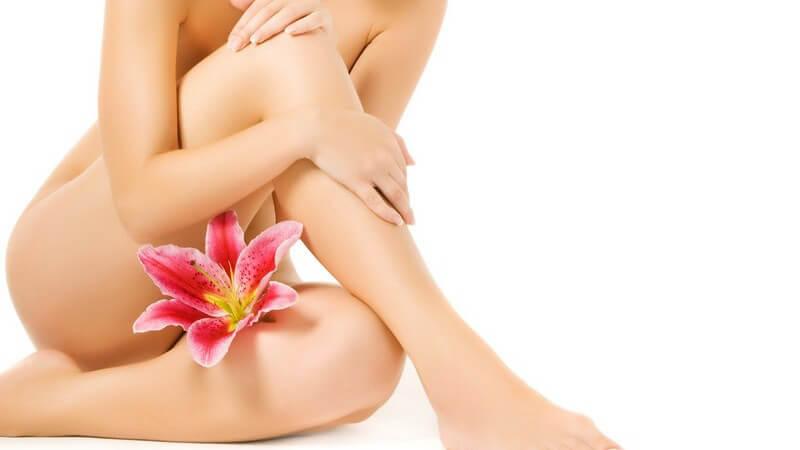 Nackter Körper einer sitzenden Frau mit rosa Lilie zwischen den Beinen