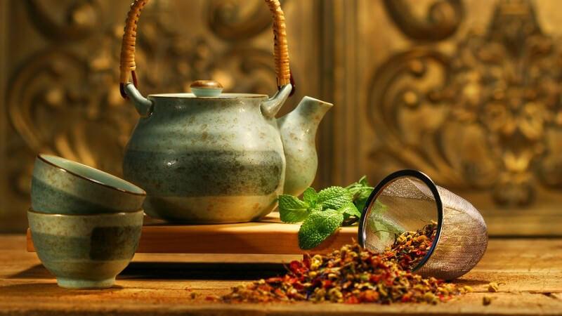 Asiatische Teekanne mit Schälchen auf Holztisch, rechts davon Teesieb und Teemischung