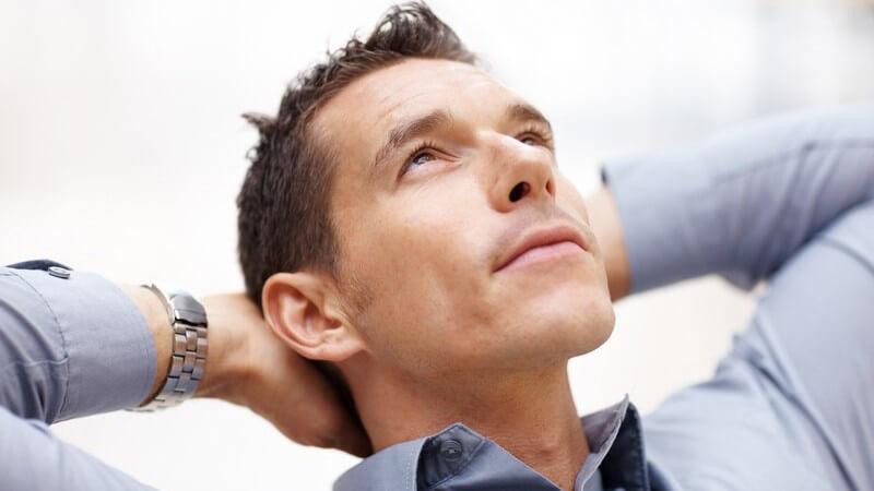 Junger Mann im Hemd zurückgelehnt, entspannt, Kopf in Handflächen gelegt