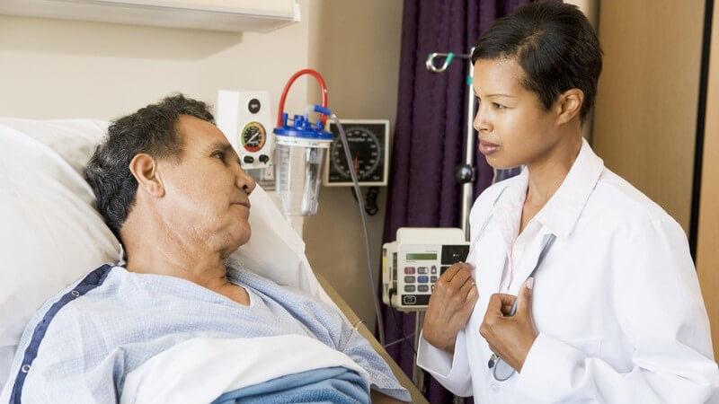 Junge Ärztin in weißem Kittel spricht mit älterem Patient, der im Krankenbett liegt