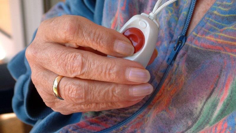 Nahaufnahme Rentnerin drückt roten Knopf auf Gerät um ihren Hals für Hilfe