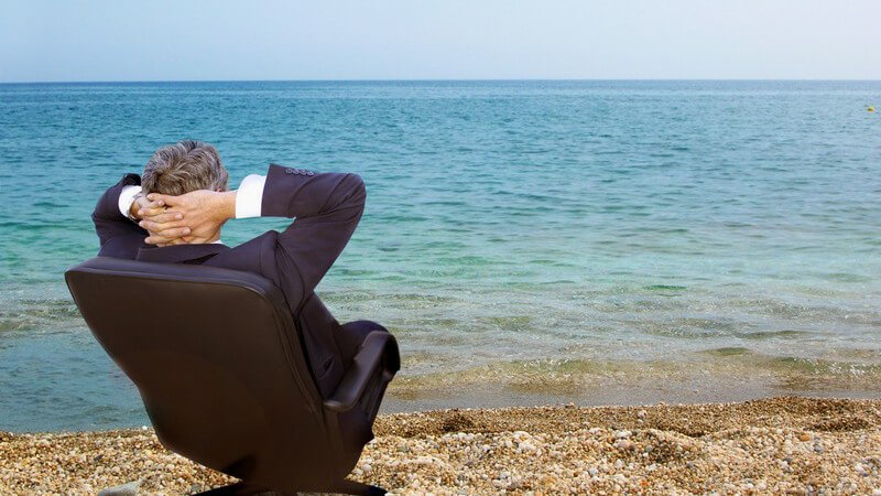 Rückansicht Geschäftsmann im Anzug sitzt auf Bürostuhl am Meer