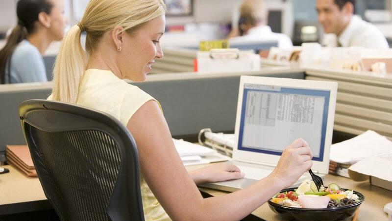 Junge Frau im Büro an ihrem PC isst Salat