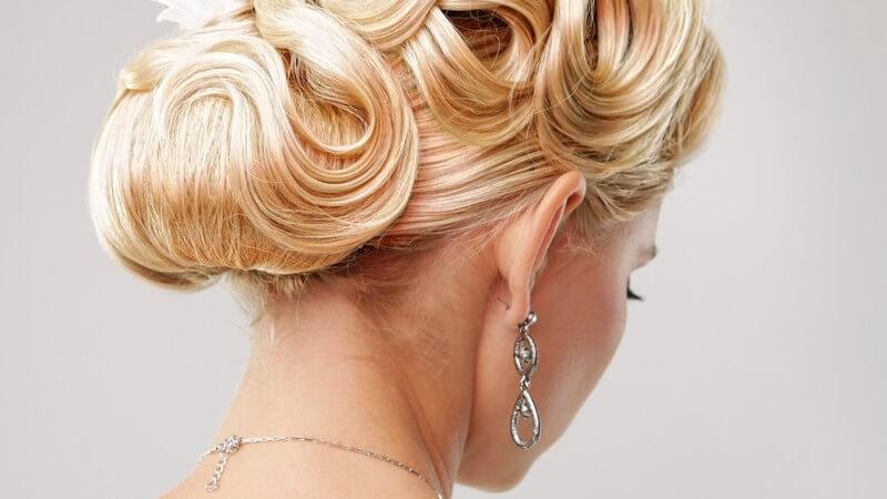 Rückansicht einer aufwändigen Brautfrisur, hochgesteckte blonde Haare mit eingearbeiteten weißen Blumen