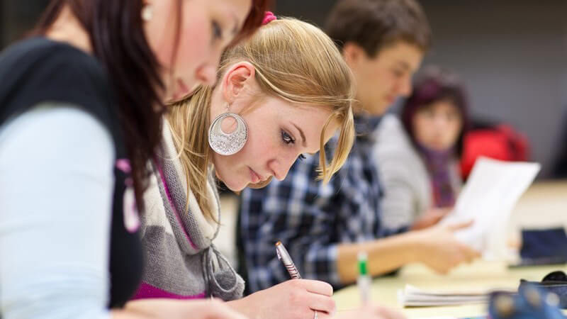 Schüler sitzen konzentriert am Tisch und schreiben