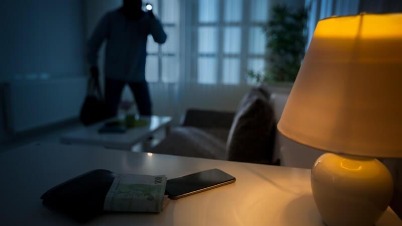 Einbrecher schleicht mit Taschenlampe durch ein Haus, Geld und Smartphone liegen auf einem Siteboard
