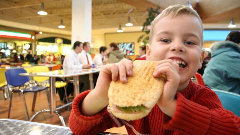 Fast Food Restaurant, kleiner Junge isst Burger