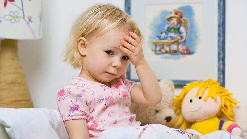 Kleines krankes Mädchen sitzt im Bett und fasst sich an den Kopf