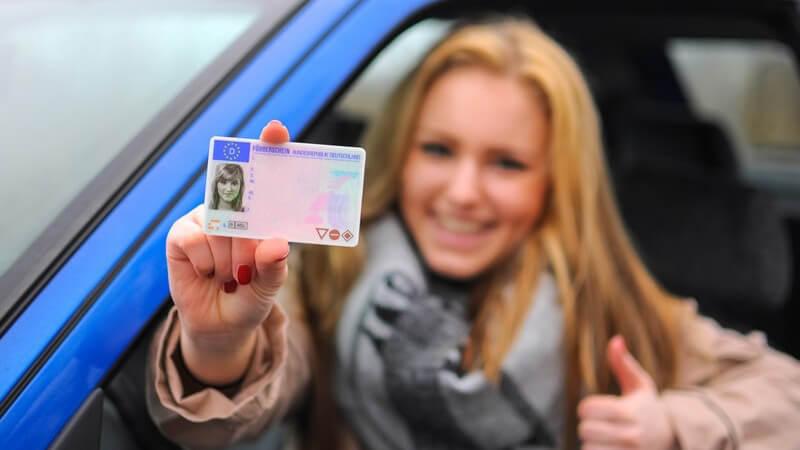Junge Frau sitzt in blauem Auto und hält stolz ihren Führerschein aus dem Fenster