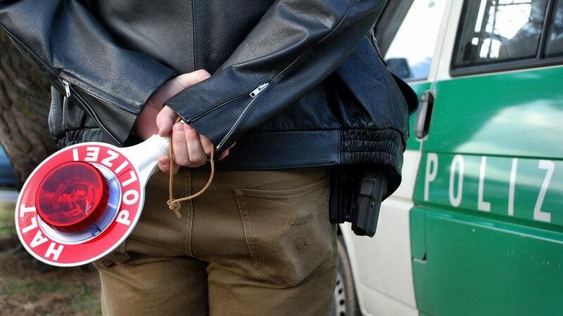 Rückenansicht Polizist, hält Kelle hinter Rücken vor einem Polizeiwagen