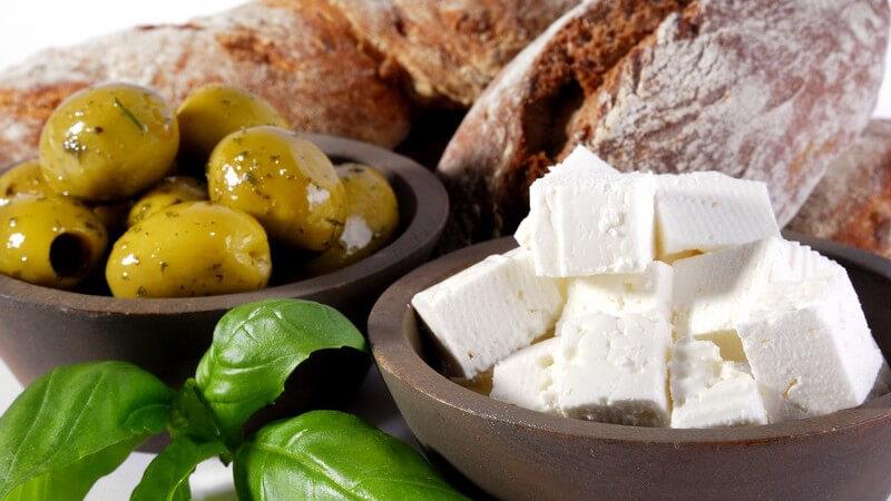 Nahaufnahme frisches Brot, Oliven, Fetakäse und Basilikumblätter auf weißem Hintergrund