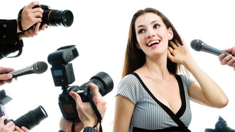 Hübsche Dame umringt von Fotografen und Mikrofonen