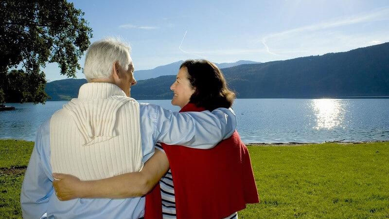 Älteres Ehepaar an Bergsee mit Sonnenschein und grüner Wiese, die Arme umeinander gelegt