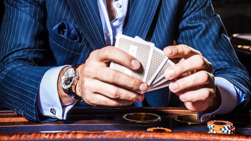Mann in blauem Nadelstreifenanzug sitzt mit Karten und Chips an einem Casinotisch