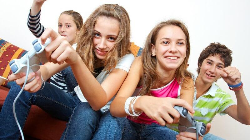 Vier Jugendliche sitzen auf Couch vor TV und spielen mit Spielkonsole