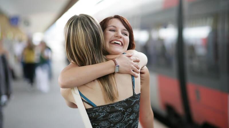2 Frauen umarmen sich auf dem Bahnsteig