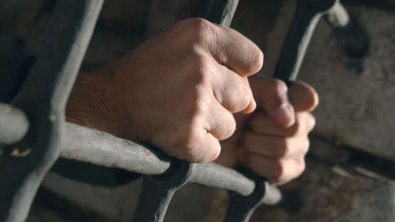 Hände eines Gefangenen halten sich an Gefängnis Gitter fest